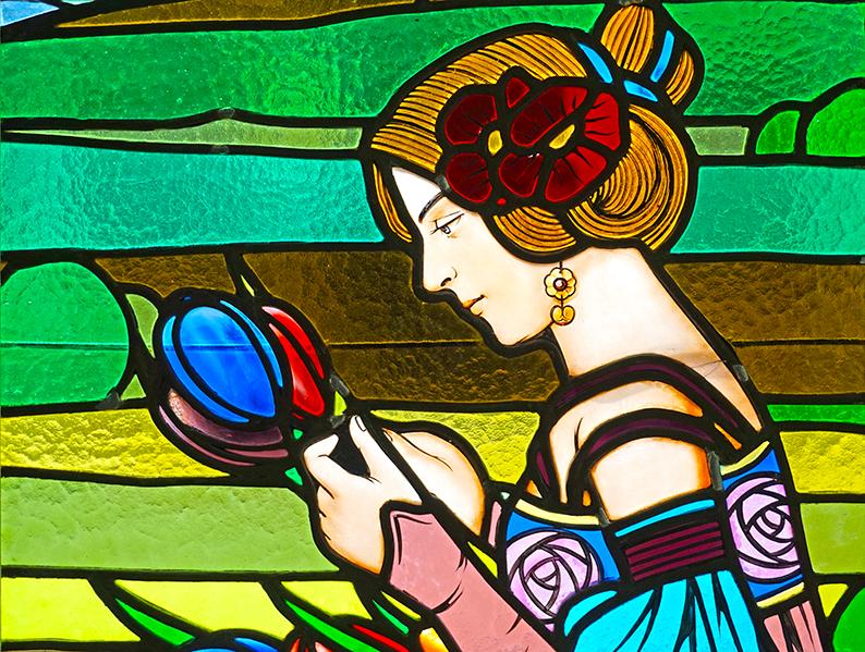 Detall d'un vitrall amb una noia agafant flors. Museu d'Art de Cerdanyola del Vallès
