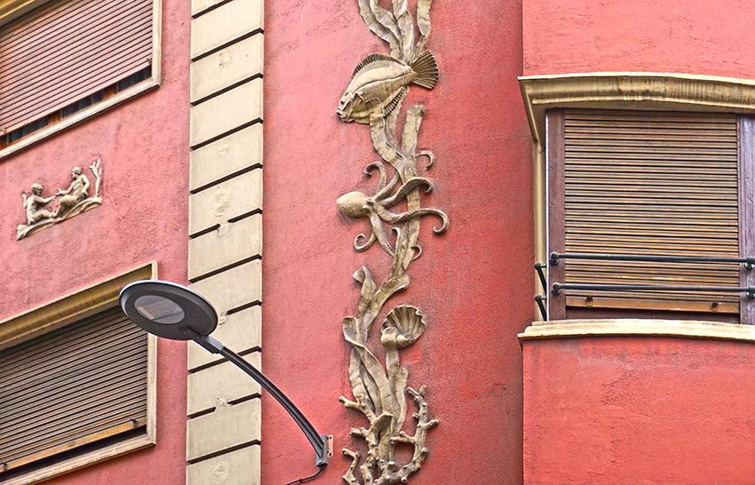 Decoració vertical en relleu amb algues, peixos i un pop. Edifici racionalista al carrer Ortigosa