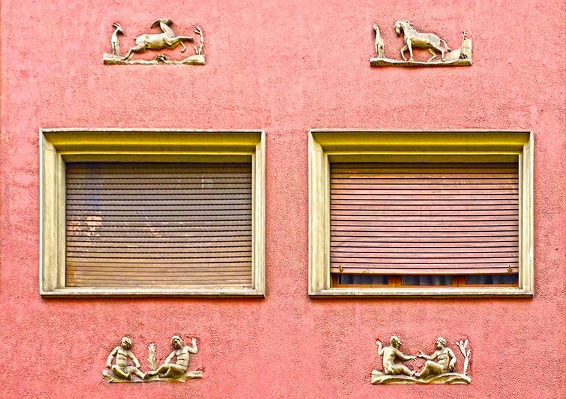 Detall de dues finestres amb petits relleus al voltant.