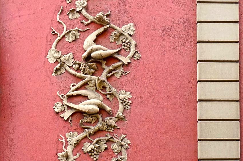 Decoració a la cantonada amb llargues branques plenes de raïm i ocells. Edifici racionalista al carrer Ortigosa