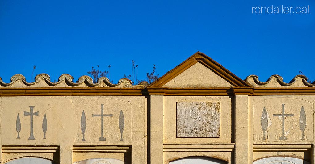 Decoració de creus entre dos xiprers al cementiri de Maià de Montcal a la Garrotxa.