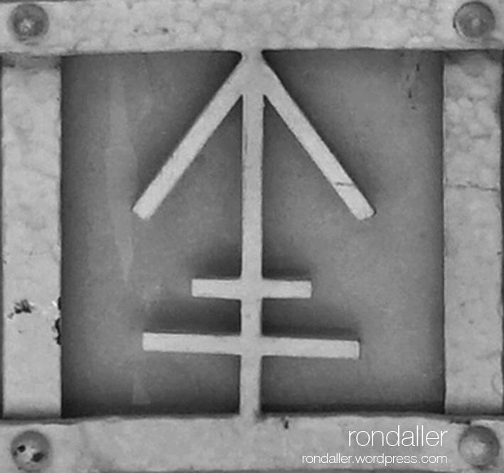 Símbols alquímics en una porta de Mataró. Maresme. Símbol del ferro.