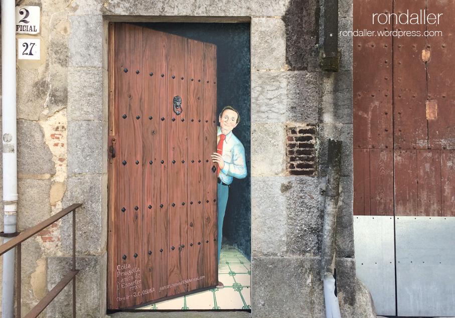 Paret amb un mural que representa una porta per on treu el nas un home. Hostalric.