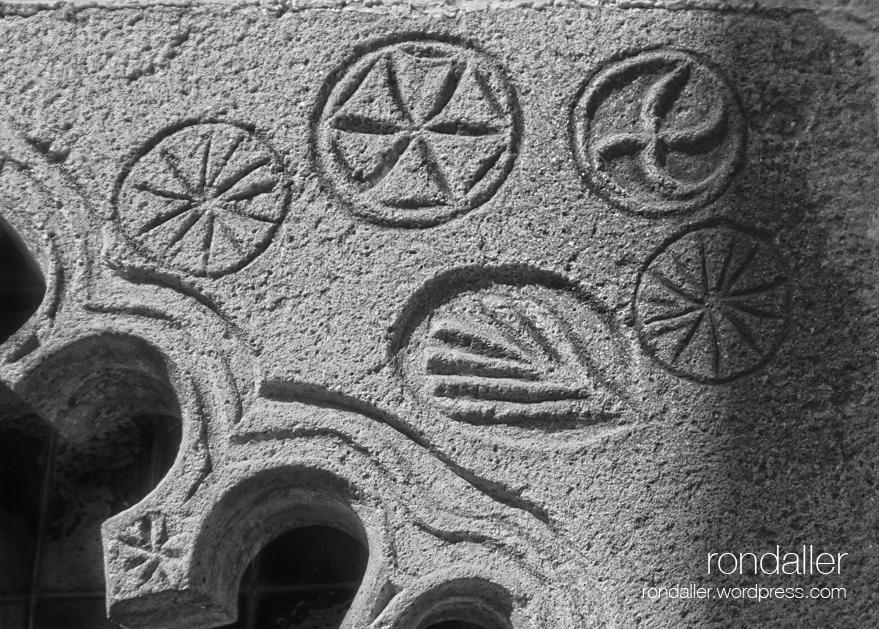 Simbols d'una finestra gòtica a Arbúcies, la Selva. Formes solars i fulla.
