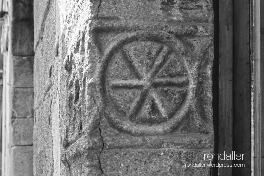Simbols d'una finestra gòtica a Arbúcies, la Selva. Forma circular.