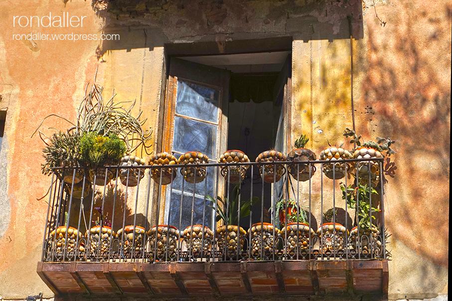 Segon itinerari per Figueres, Alt Empordà. Balcó a la plaça de les Patates, amb testos decorats amb petxines.