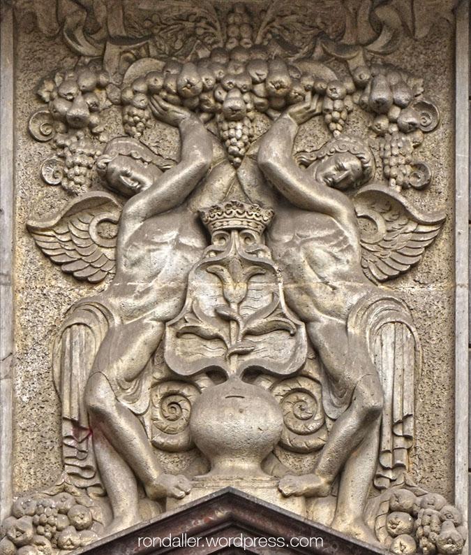 Relleu a la façana d'una entitat bancària, amb dos àngels sostenint fruites i altres elements relatius a l'estalvi.