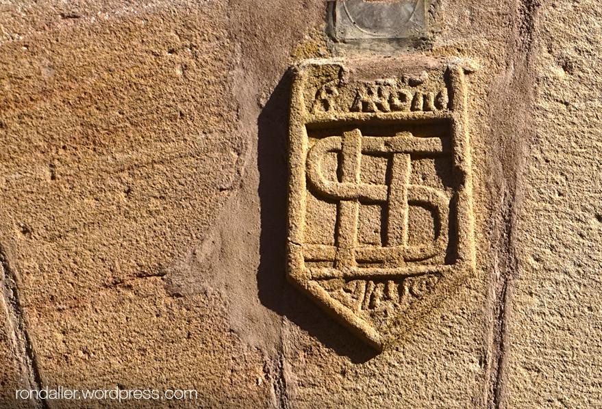 Itinerari per Seva, Osona. Dovella d'un portal amb el monograma IHS.