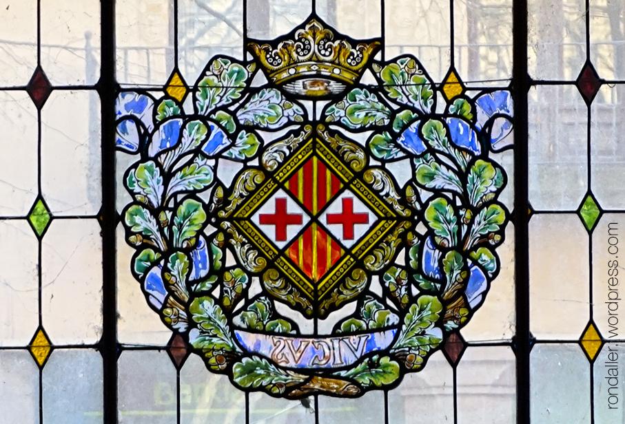 La Casa Illa de Vic (Osona). Vitrall amb l'escut de la ciutat a les Galeries Montseny.