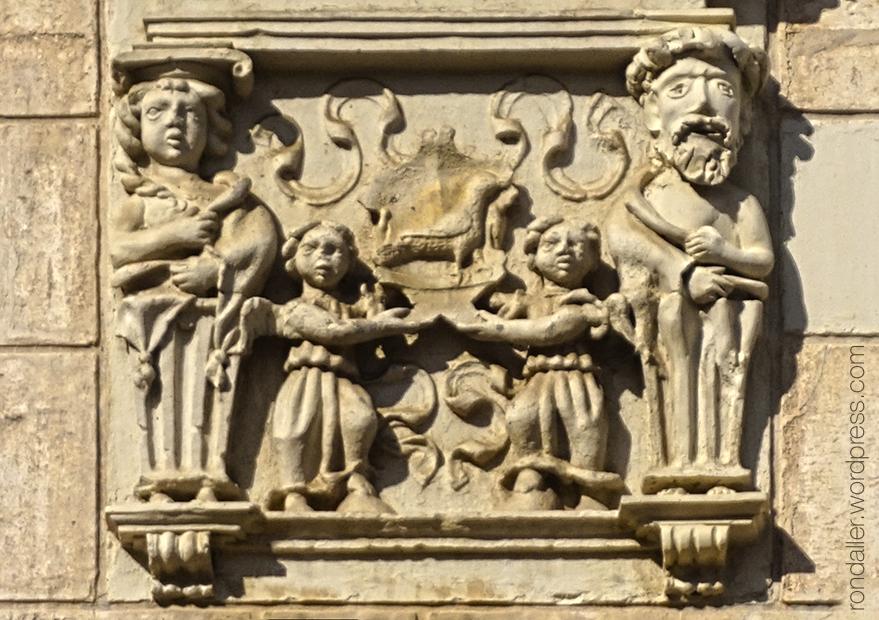 Decoració en relleu que representa uns personatges portant l'escut dels Moixó.