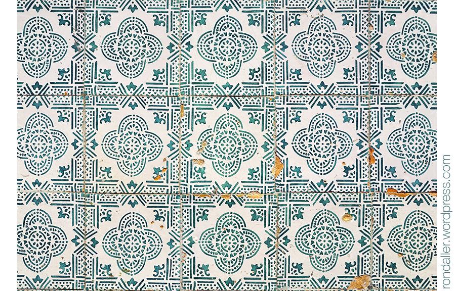 Rajola amb un motiu repetitiu de color verd sobre fons blanc.