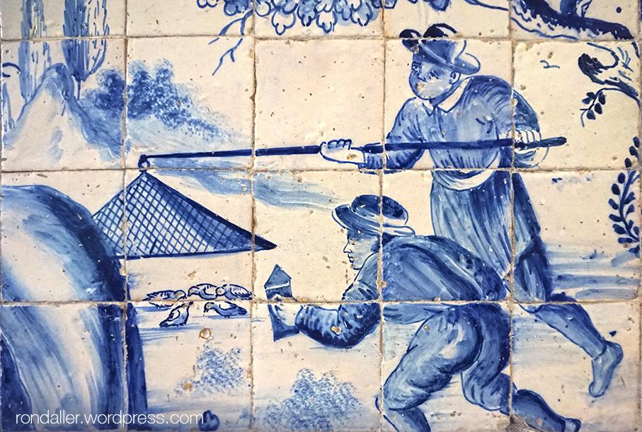Detall d'un mural ceràmic que representa dos personatges a punt d'atrapar un grapat d'ocells.
