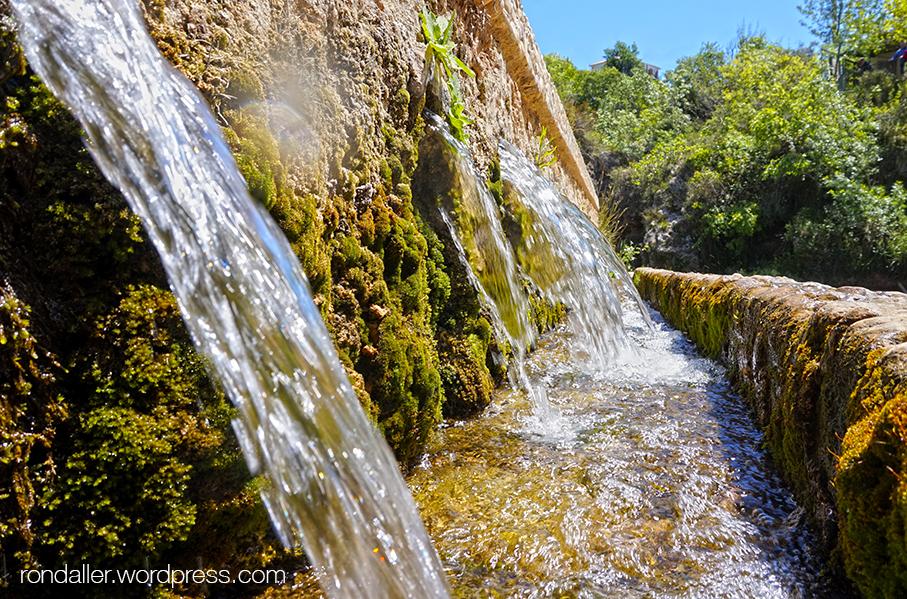 Aigua rajant pels brocs de la font.