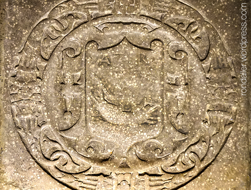 Detall d'un escut desgastat en una llosa funerària.