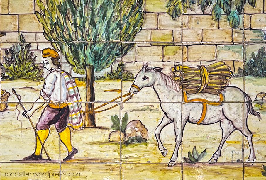 Detall del mosaic amb un personatge amb un ase transportant llenya.