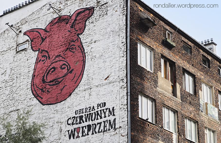 Cara d'un porc de color vermell pintat en una mitgera d'un edifici.
