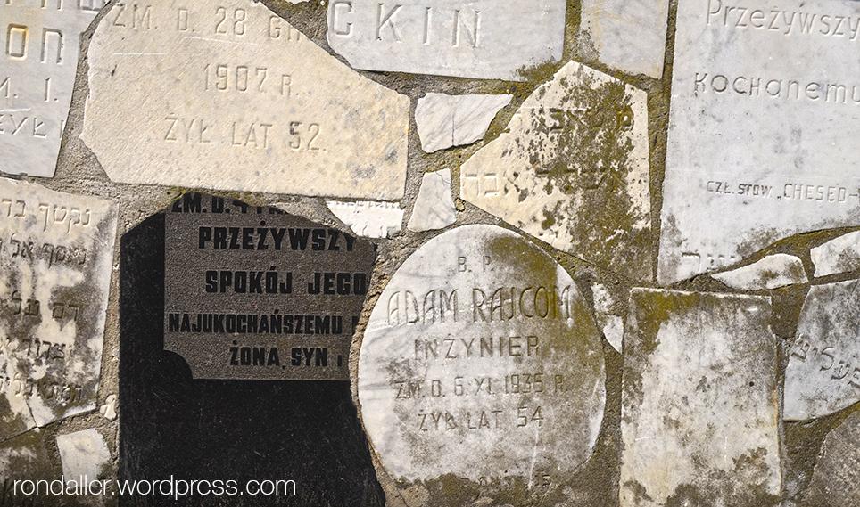 Trossos de lloses funeràries en un mur.