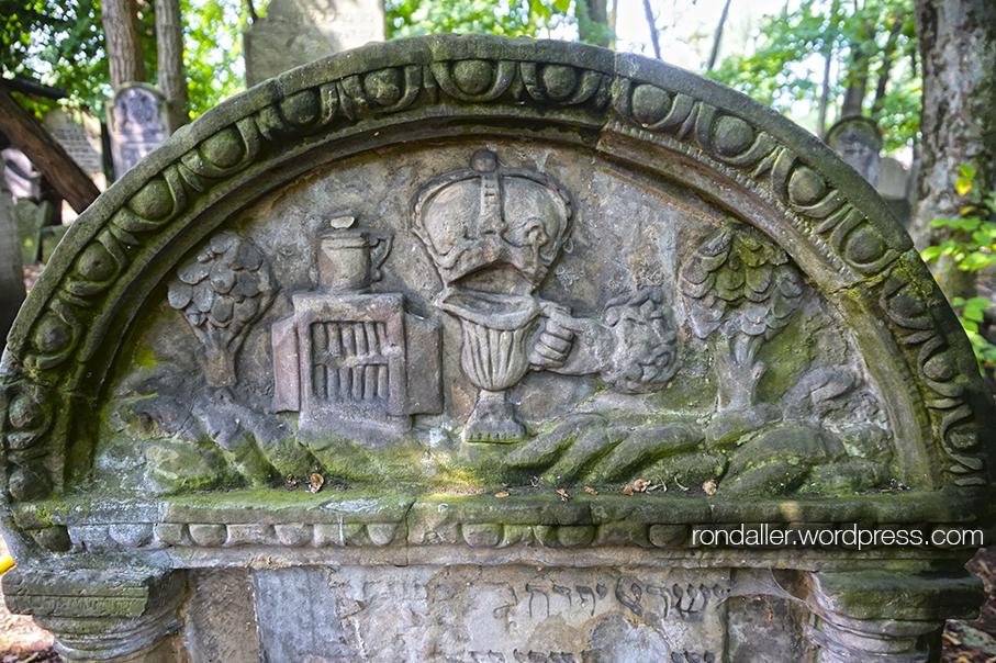 Cementiri jueu de Varsòvia. Representació de diversos elements, com una gerra, arbres, una corona i un armariet amb llibres.