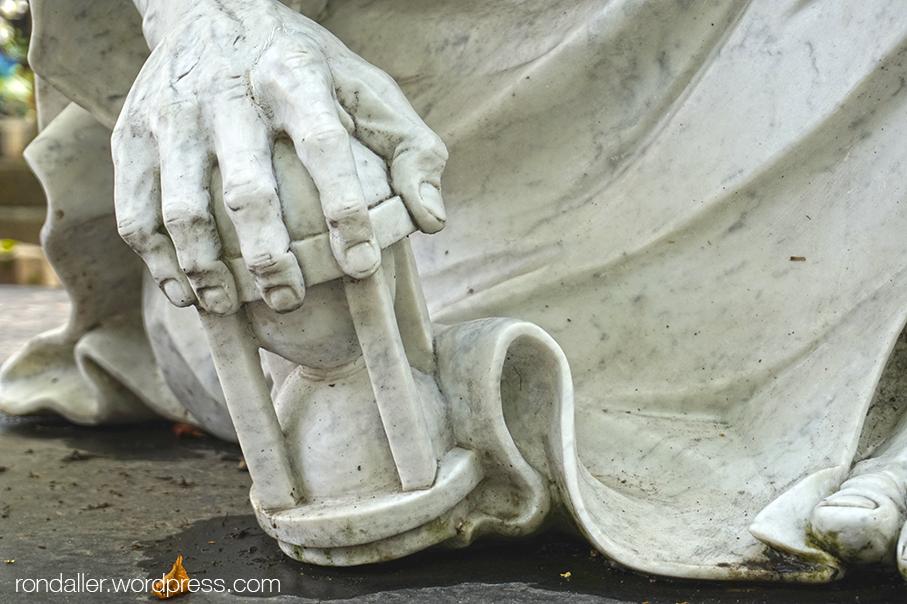 Itinerari per Varsòvia. Detall d'una escultura on es veu una ma agafant un rellotge de sorra, al Cementiri Vell de Powązki.