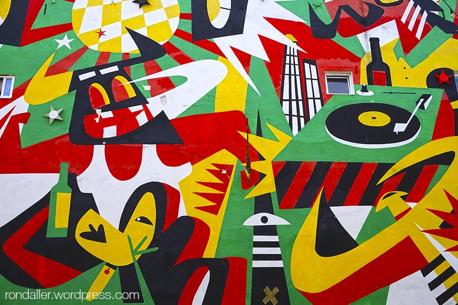 Ruta per Varsòvia. Mural de colors llampants, que ocupa la mitgera d'un edifici i representa un ambient musical.