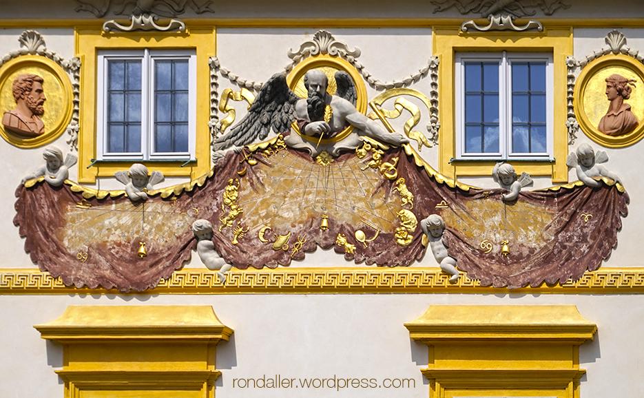 Gran rellotge de sol al Palau Wilanów on un personatge amb ales esten una gran peça de roba.