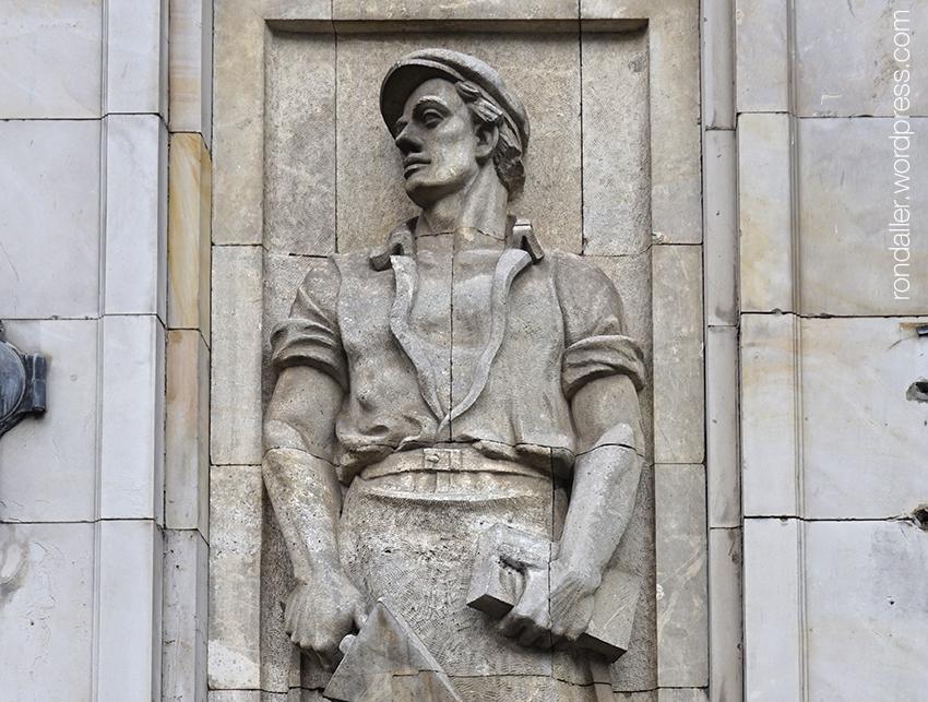 Itinerari per Varsòvia. Escultura d'un paleta en un edifici de l'època socialista de la plaça Konsztitucji.