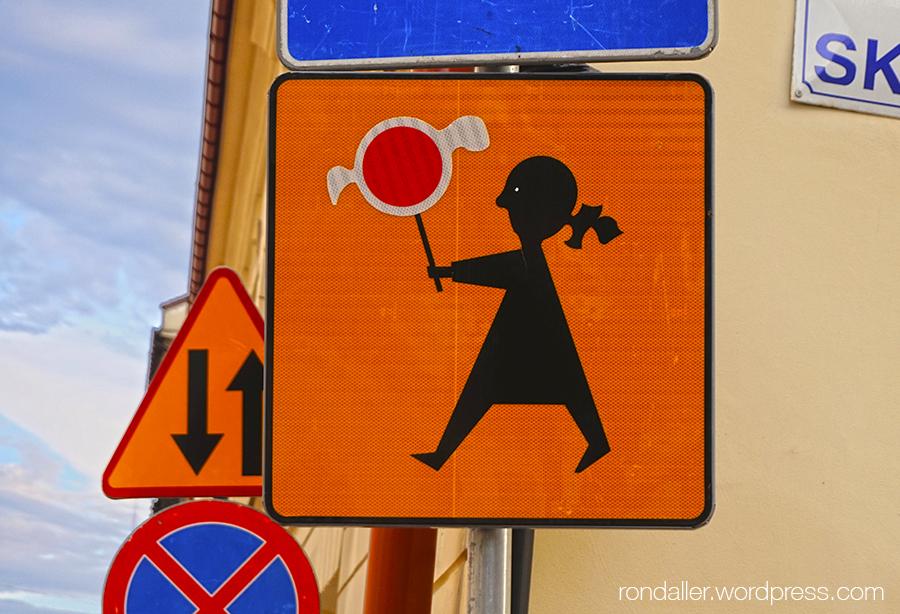 Diversos senyals de trànsit. En un es veu una nena caminant amb un senyal rodó a les mans.