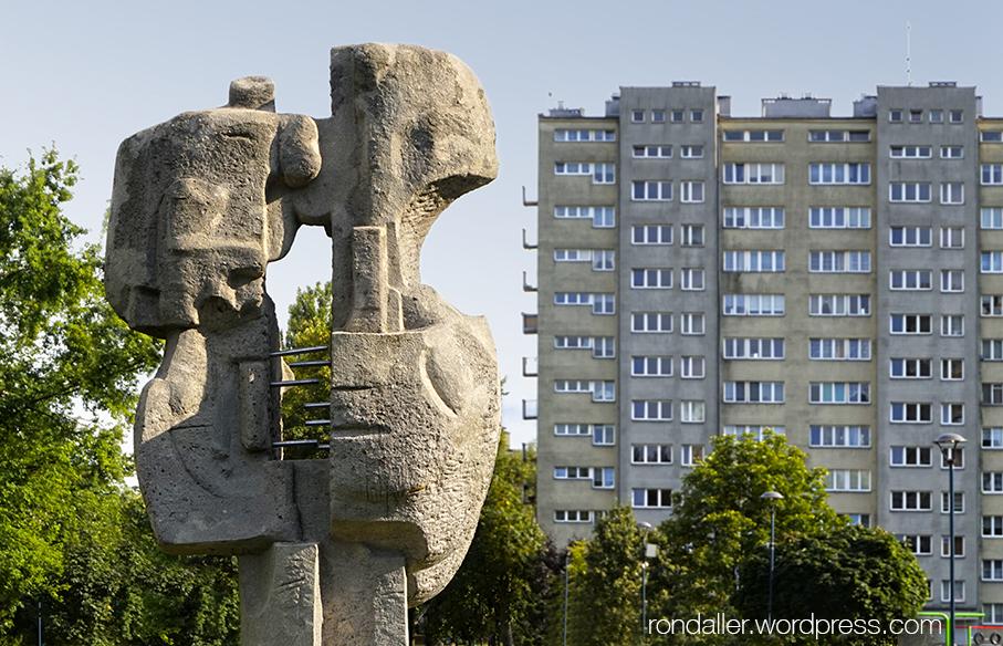 Itinerari per Nowa Huta. Escultura abstracte en un parc amb un bloc gris de fons.