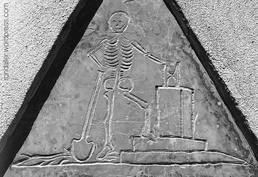 Llosa funerària on hi ha gravat un esquelet dempeus amb una pala en una ma i un rellotge de sorra a l'altra.