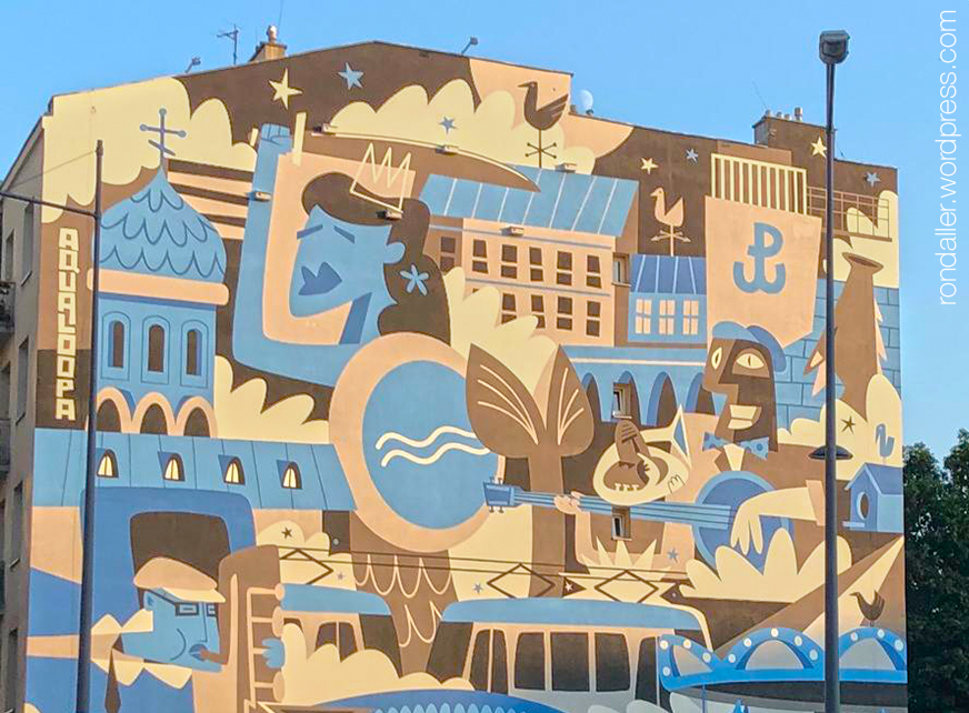 Itinerari per Varsòvia. Mural que cobreix la mitgera d'un edifici, representant diversos símbols de la ciutat.