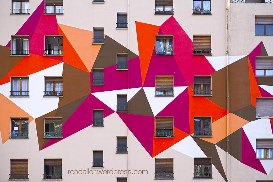 Mural de formes geomètriques que cobreix la façana d'un gran bloc d'habitatges.