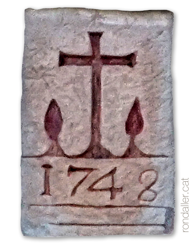 Relleu d'una creu entre xiprers a Cal Coronel, a la sagrera de Sant Feliu de Codines.