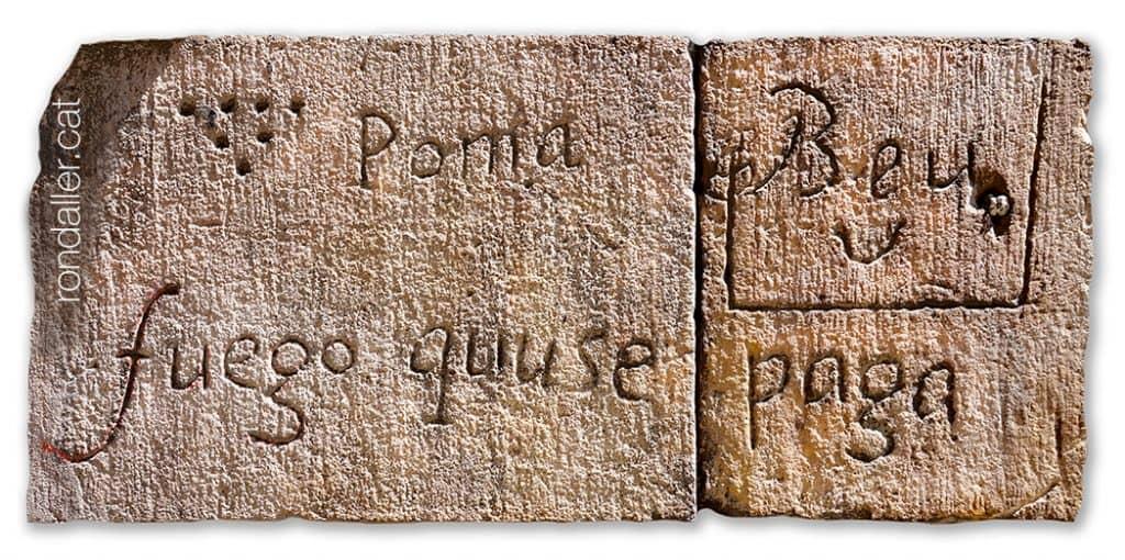 """Inscripcions en uns carreus amb el text """"fuego que se paga, Poma, i altres símbols i lletres."""