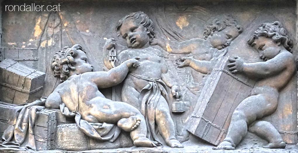 Porxos den Xifré. Relleu de terracota amb uns infant en un moll pesant i carregant caixes.