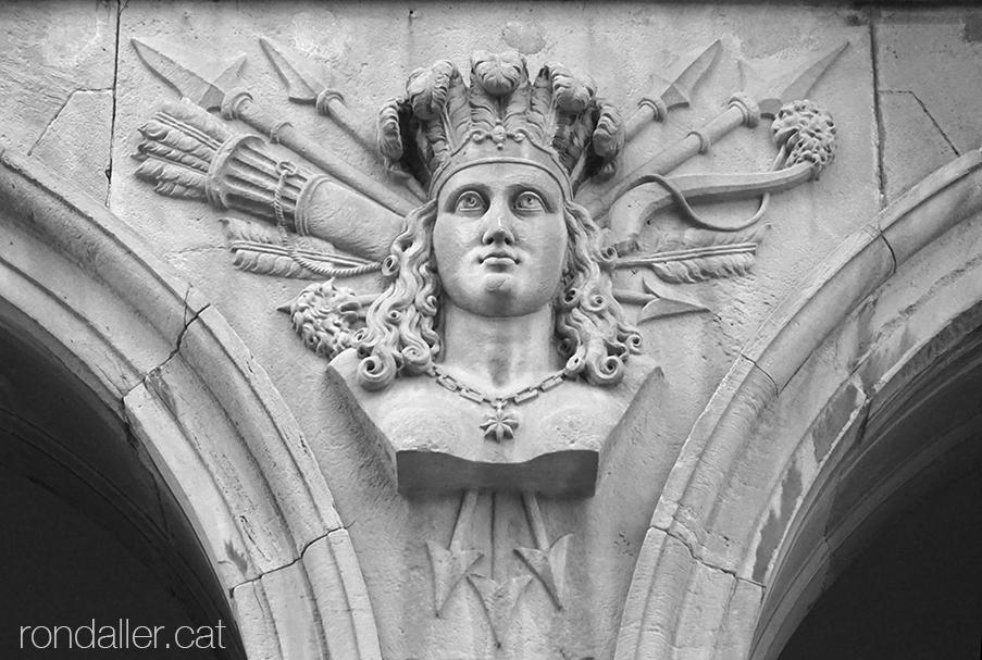 Porxos den Xifré. Bust femení amb una corona de plomes i amb diversos atributs indígenes, com fletxes i llances.