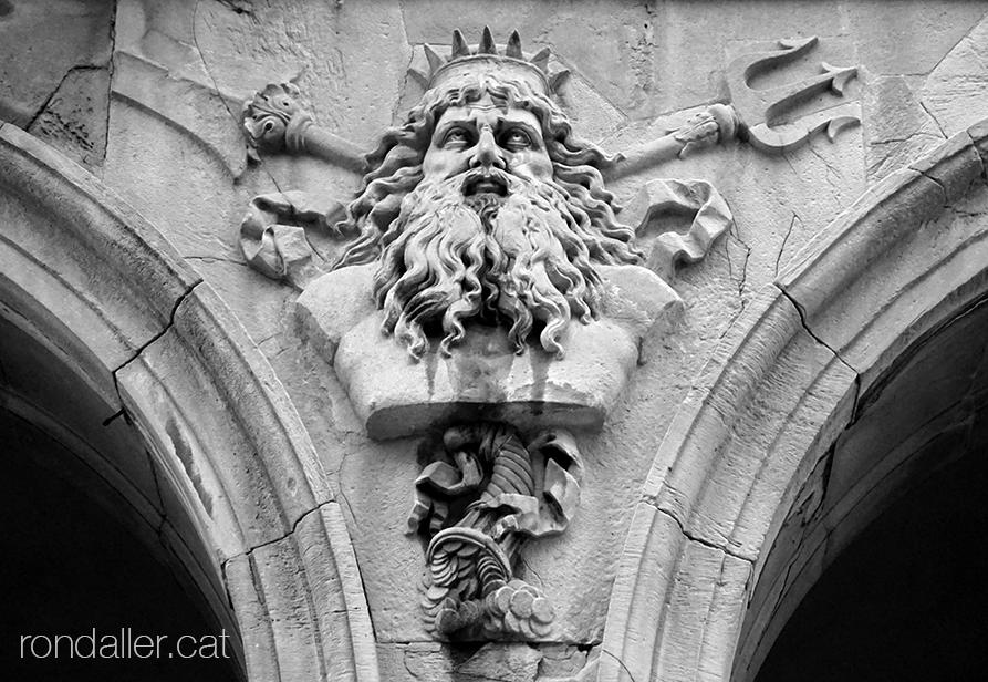 Porxos d'en Xifré. Cap del déu Posidó amb una corona, barba, trident i una cornucòpia amb monedes.