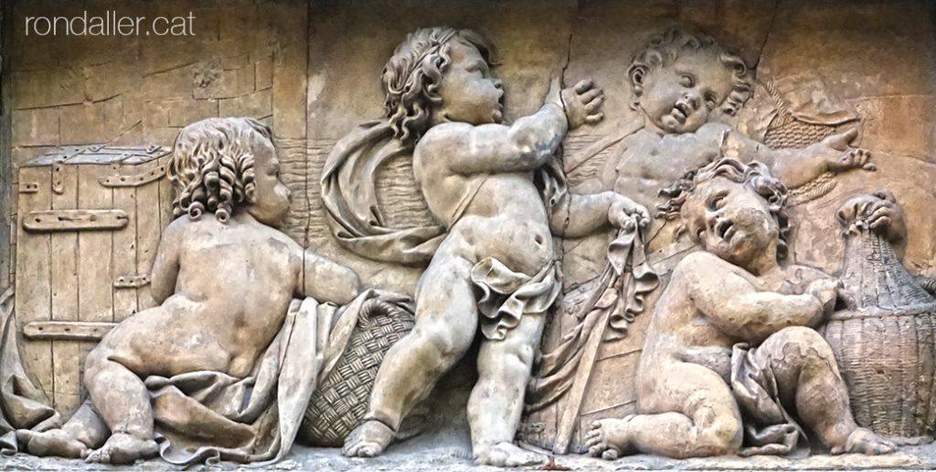 Porxos d'en Xifré. Plafó ceràmic amb unes figures infantils entre caixes, cistells i gerres.