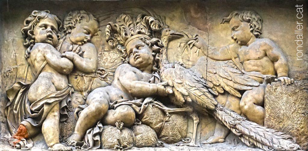 Porxos d'en Xifré. Relleu de terracota atribuit a Damià Campeny, amb un infant amb corona de plomes i un gall dindi.
