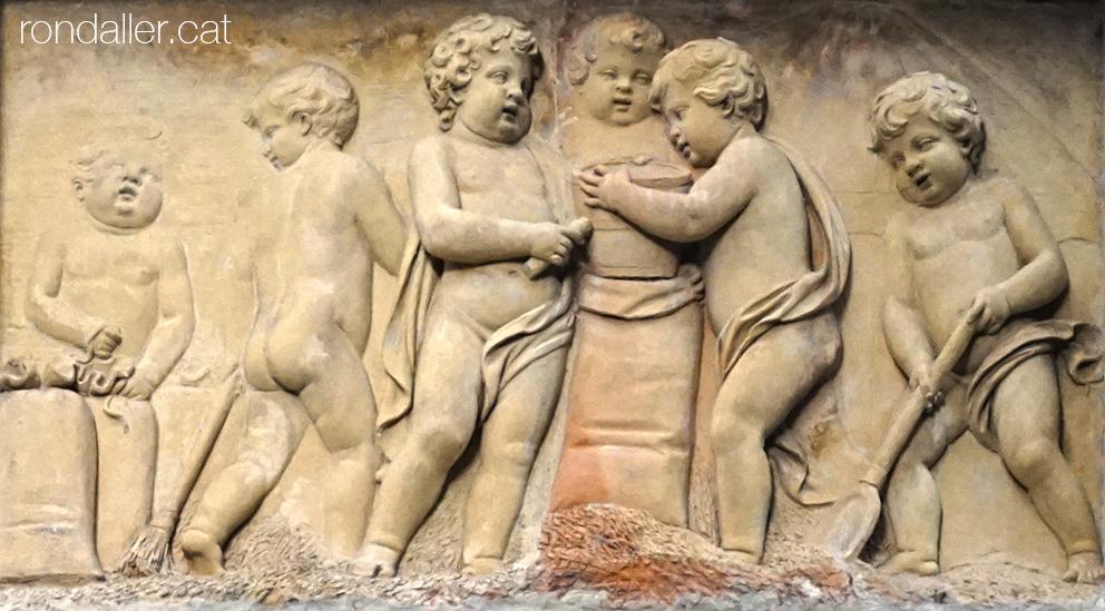 Porxos d'en Xifré. Relleu de terracota amb sis figures infantils emplenant i lligant sacs.