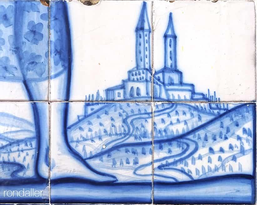 Font de Santa Anna. Detall del plafó ceràmic omn es veu el peu d'una figura i un poblet amb dos campanars.