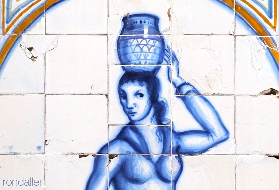 Detall del plafó ceràmic realitzat per Josep Aragay on es veu una figura femenina amb una gerra al cap.