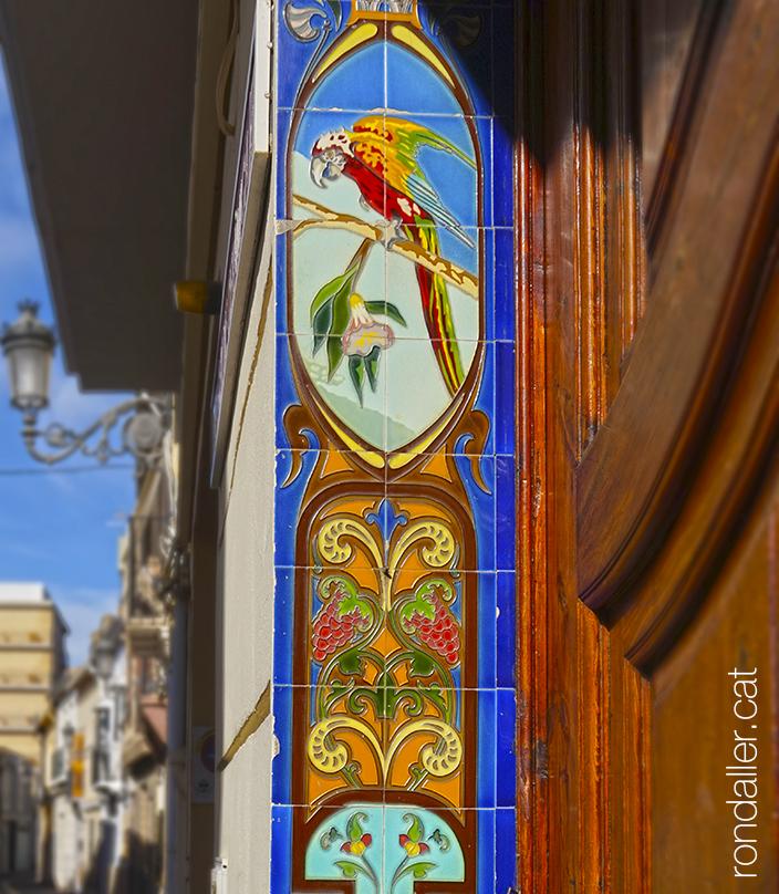 Brancal ceràmic d'una porta decorat amb un acolorit guacamai i altres elements florals.