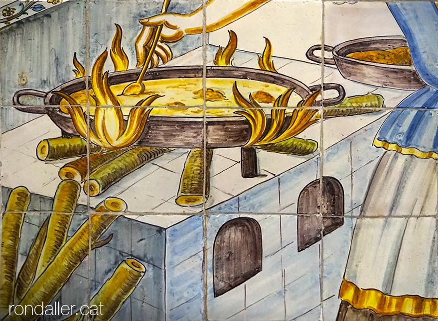 Rajoles de Manises. Detall d'un mural ceràmic de José Gimeno Martínez on es veu una dona cuinant una paella.