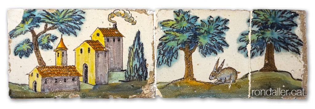 Rajoles que es col·locaven als graons de les escales, on es veu un poble, arbres i un conill.