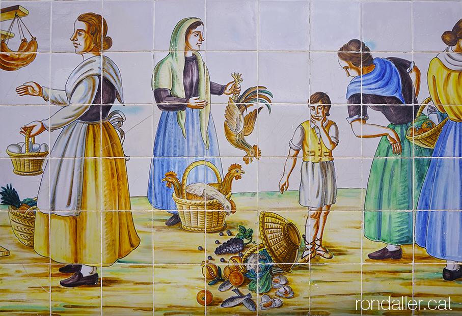Rajoles de Manises. Mural ceràmic de José Gimeno amb persones amb vestits tradicionals venent al carrer.