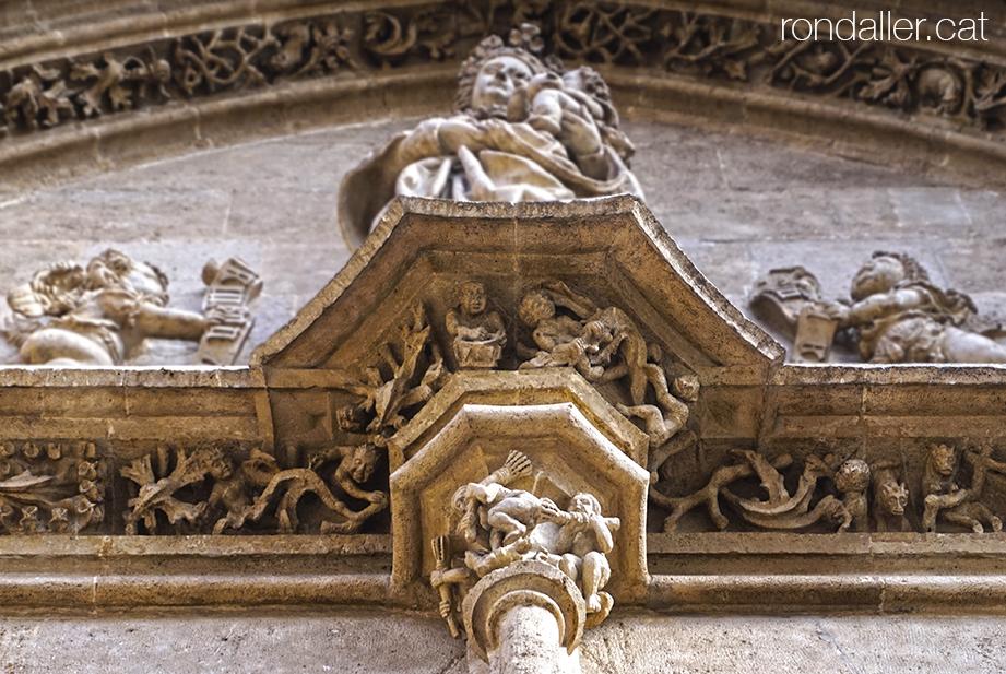Portalada de la Llotja de la Seda de València amb detalls escultòrics de bruixes i personatges pecaminosos.