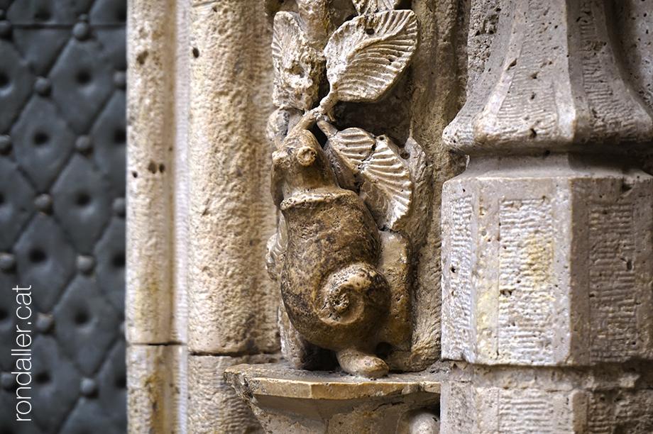 Detall del relleu escultòric a l'entrada de la Llotja que representa un cargol passant, símbol de la peresa.