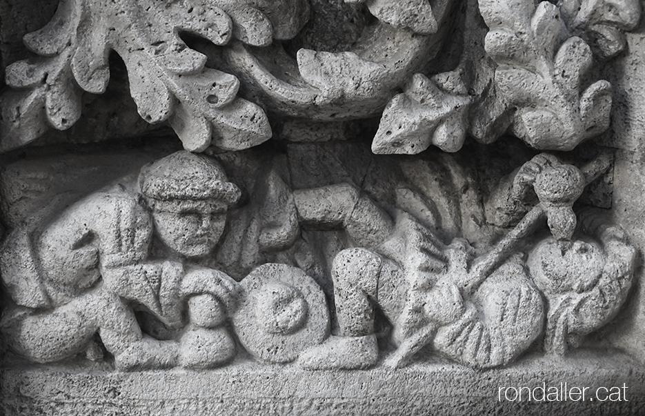 Representació de la mandra a la Llotja de la Seda de València, amb un personatge estirat al terra i un altre assegut.