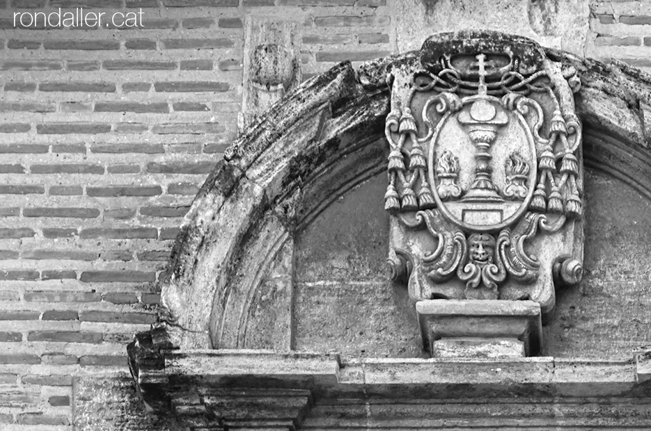 Escut del col·legi Corpus Christi damunt la portalada de l'església de Sant Bartomeu.