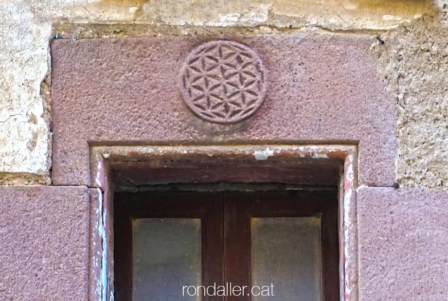 Llinda d'una finestra de la sagrera amb un cercle gravat amb l'anomenada flor de la vida.